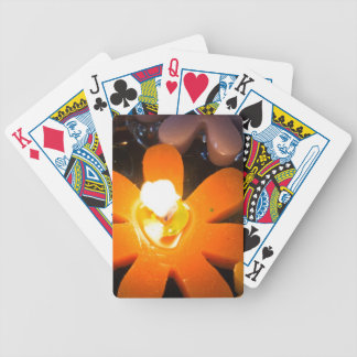 Flame from an orange floating candle bicycle poker deck