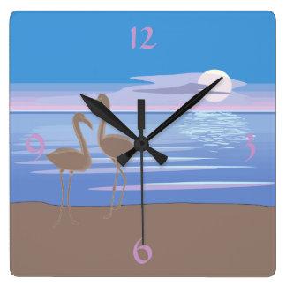 Flamencos en la playa reloj cuadrado