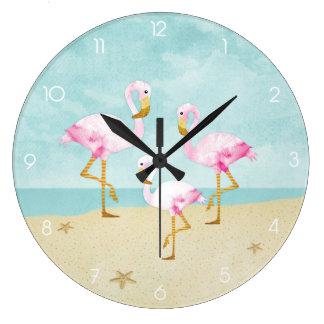 Flamencos rosados de la acuarela en la playa reloj redondo grande