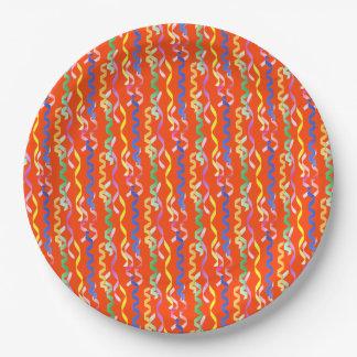 Flámulas multicoloras del fiesta en un naranja de plato de papel de 9 pulgadas