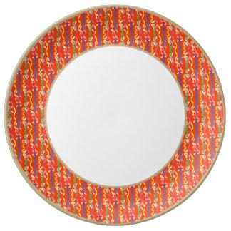 Flámulas multicoloras del fiesta en un naranja de platos de cerámica