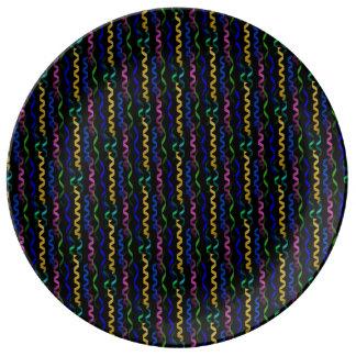 Flámulas multicoloras del fiesta en un negro platos de cerámica