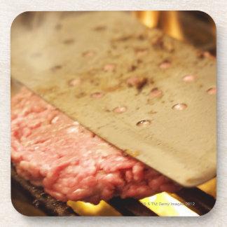 Flattening a Hamburger Patty with a Spatula on Beverage Coaster