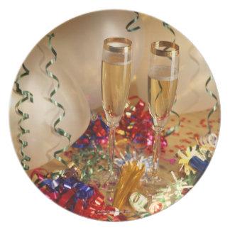 Flautas de champán, flámulas y noisemakers platos de comidas