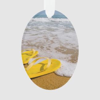 Flips-flopes amarillos en la playa