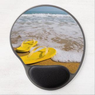 Flips-flopes amarillos en la playa alfombrilla gel