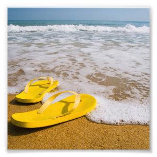 Flips-flopes amarillos en la playa fotografías