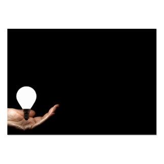 Floating lightbulb above hand on black background large business card