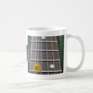 Flor amarilla bonita en fretboard bajo taza de café
