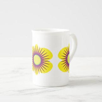 Flor amarilla y púrpura de la primavera en modelo taza de porcelana