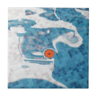 Flor anaranjada flotante de la primavera en agua a azulejo