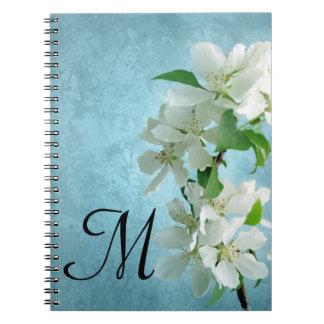 Flor blanca en el cuaderno azul de la inicial del