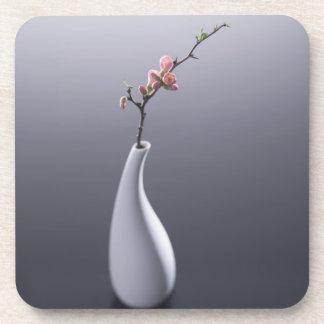 Flor de cerezo en florero posavasos