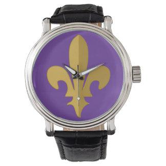 Flor de lis del oro en el reloj púrpura de la
