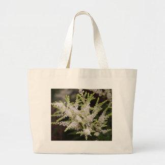 flor en el jardín bolsas de mano