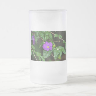 Flor púrpura bonita contra fondo oscuro taza cristal mate