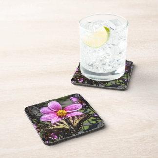 Flor púrpura brillante con la mariposa en los péta posavasos de bebida