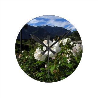 Floraciones del rosa blanco en un fondo de la reloj redondo mediano