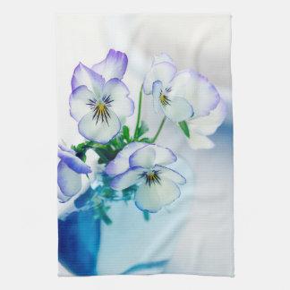 Florero azul de las flores púrpuras blancas de los toallas de cocina