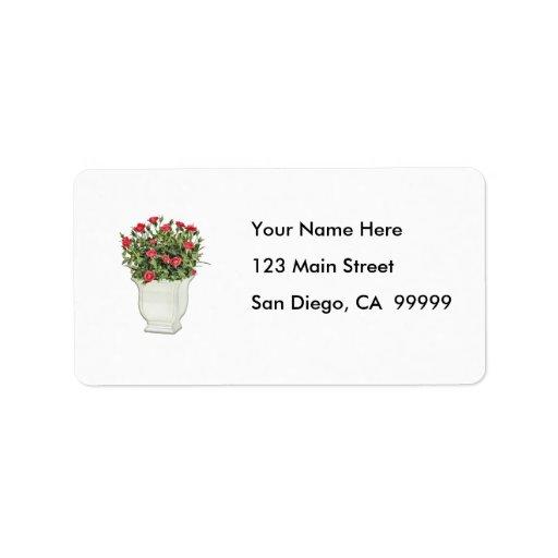 Florero blanco de rosas rojos etiqueta de dirección