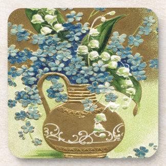 Florero de flores azules y blancas posavasos de bebida