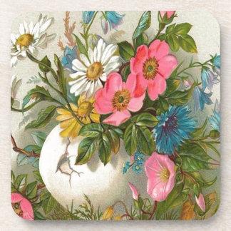 Florero de flores rosadas, blancas y azules posavaso