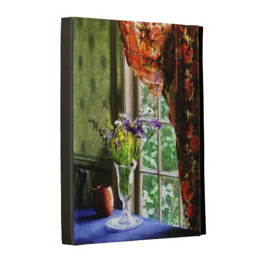 Florero de la flor y de la taza por la ventana
