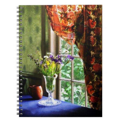 Florero de la flor y de la taza por la ventana libro de apuntes con espiral