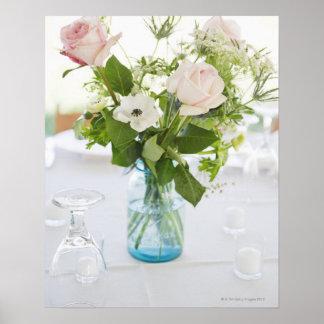 Florero de rosas en la tabla de cena del sistema póster