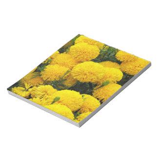 Flores amarillas brillantes en la libreta bloc de notas