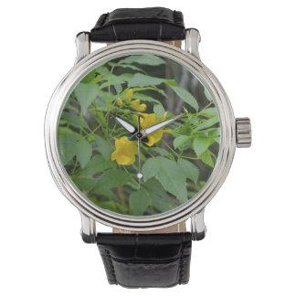 flores amarillas contra las hojas verdes relojes de pulsera