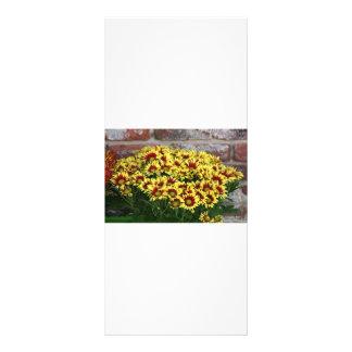 Flores amarillas rojas contra la pared de ladrillo plantillas de lonas
