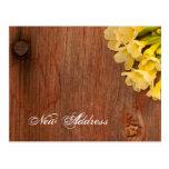 Flores amarillas y postal de madera de la direcció