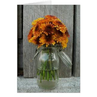 Flores anaranjadas en tarjeta del tarro de albañil