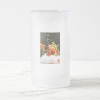 Flores anaranjadas y cierre aherrumbrado de la taza de cristal