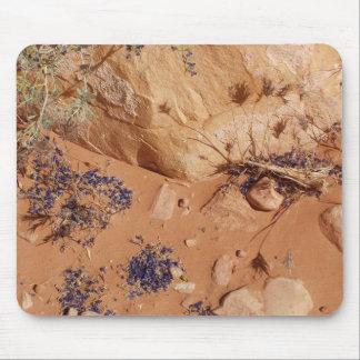Flores azules en la arena roja alfombrillas de ratón