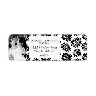 Flores blancas negras enrrolladas que casan la eti etiquetas de remite