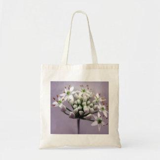 Flores blancos de la cebolleta de ajo en púrpura bolsas lienzo