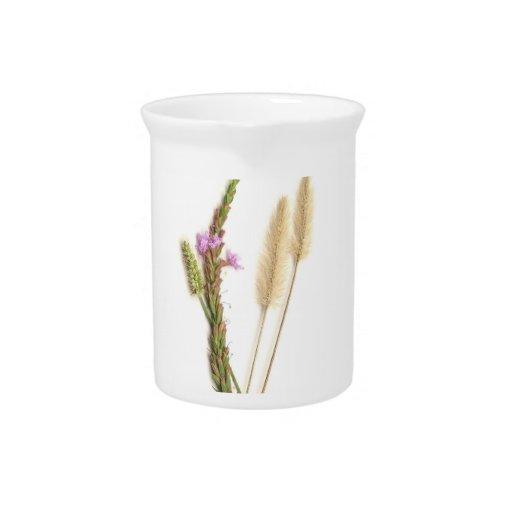 Flores borrosas y púrpuras con los troncos verdes jarra de beber
