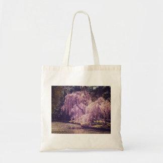 Flores de cerezo en los árboles al lado de una cha bolsas