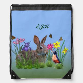 Flores de la primavera, petirrojo, y conejo de mochilas