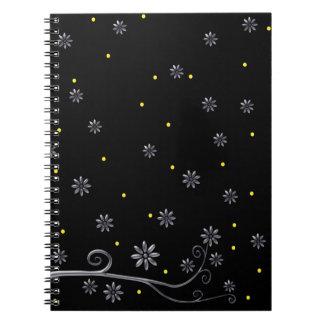 Flores de plata elegantes en el cuaderno negro