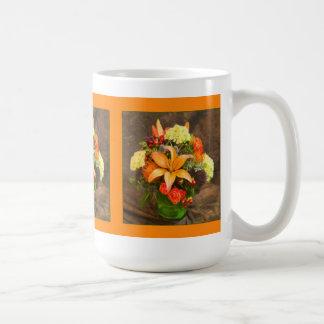 Flores del otoño de rosas y de la taza de los