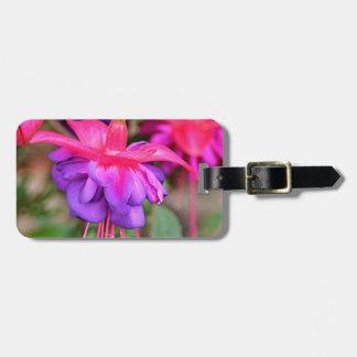 Flores fucsias rosadas y púrpuras en la floración etiqueta para maleta