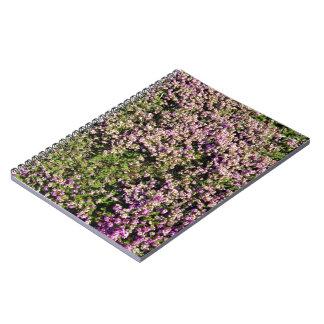 Flores púrpuras bonitas en la cubierta de tierra libreta espiral