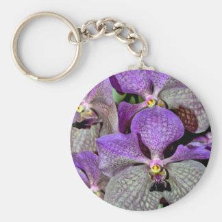 Flores púrpuras de la orquídea de polilla en la llavero redondo tipo pin