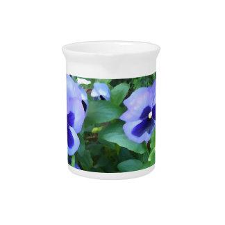 Flores púrpuras de los pensamientos del jardín de  jarra de beber
