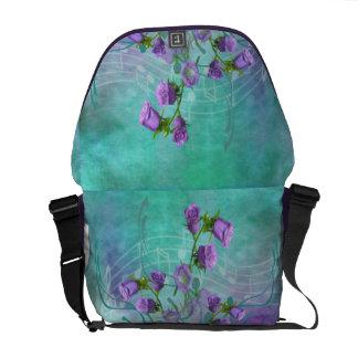 Flores púrpuras y notas musicales bolsas de mensajería