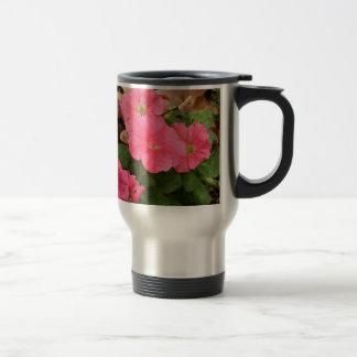 Flores rosadas de la petunia en la floración taza de viaje