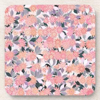 Flores rosadas en un fondo de las hojas de plata posavaso